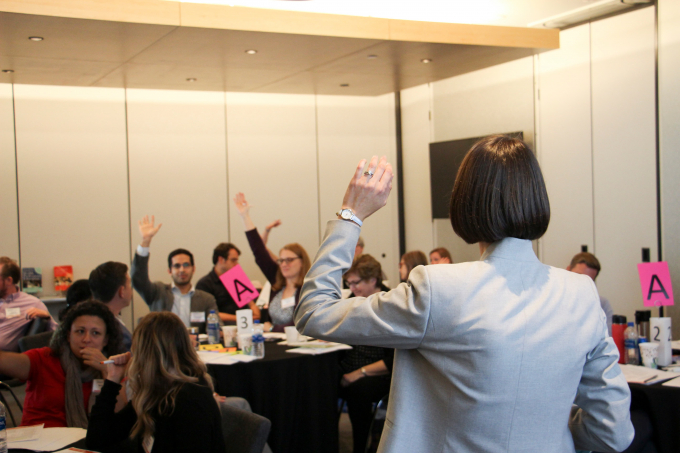 participants in a room raising their hands